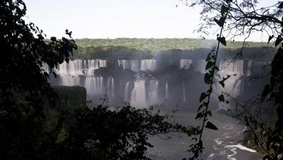 Medium wide angle dawn over large section of Iguazu Falls framed by forest