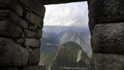 Wide angle view through Machu Picchu stone window to mountains beyond with rolling clouds