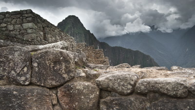 Wide angle jib shot up and over stone parapet to reveal stone terraces, mountains and clouds beyond