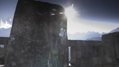 Wide angle track through roofless stone building with cloud overhead as sun dramatically emerges from cloud