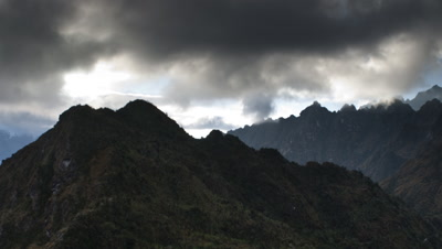 Wide angle broody storm clouds hover around hilly peaks then sun bursts through on Inca Trail
