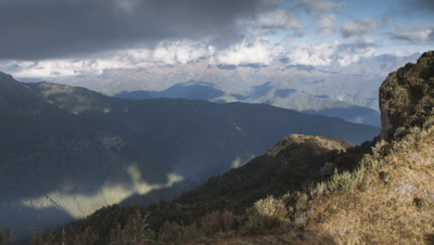 Big wide angle establisher from peak on the Inca Trail across mountains and valleys into far distance with bubbling white clouds