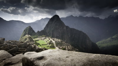 Wide angle track along stone wall to reveal classic view over Machu Picchu with mountain backdrop and dark cloud overhead