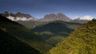Wide angle establisher of Manu cloud forest with swirling clouds racing through forested mountain valley