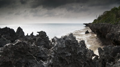 Wide angle track along coral rag shoreline with dark stormy sky over sea