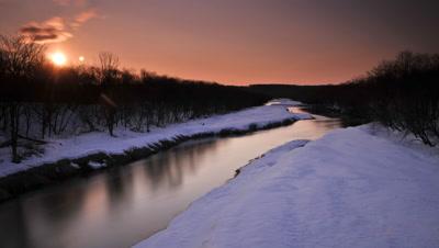 Orange sunrise over winter forest and river from Otowa Bridge, Tsurui, Hokkaido, Japan