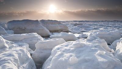 Sunrise through clouds as camera tracks past frozen sea, Monbetsu, Hokkaido, Japan