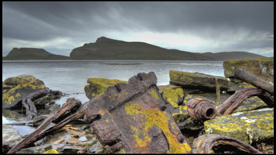 Grey clouds brew over whaling station and rusting harpoon on New Island, Falklands