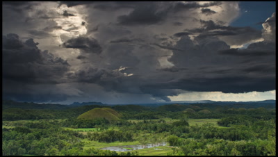 Clouds and rain drift across Chocolate Hills in Bohol Province, Philippines