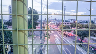 High tracking shot from pedestrian bridge of Manaus traffic from day to night, Brazil