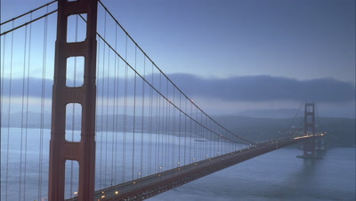 Wide angle view of Golden Gate Bridge spanning Bay in early evening with fog rolling in which then lifts