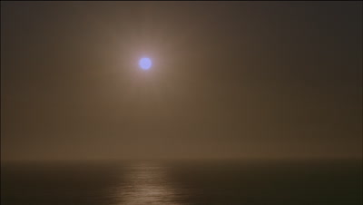Wide angle sun sets into Pacific Ocean obliquely through frame; starts blue grey then to orange then black