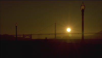 Wide angle sun sets behind long view of Golden Gate Bridge with pedestrians on bayside sidewalk