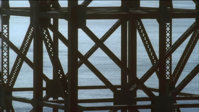 Mid shot view to tide race through Golden Gate bridge pilings