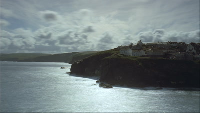 Wide angle clouds race over coastal headland with traditional cottages and blue sky with waves crashing on rocks