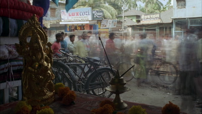 Medium wide angle looking out of market stall shrine to Ganesh to busy street scene with parked bicycles and streaming pedestrians