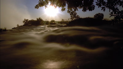 Mid shot setting sun over top of Victoria Falls with motion blur water flow in soft evening light