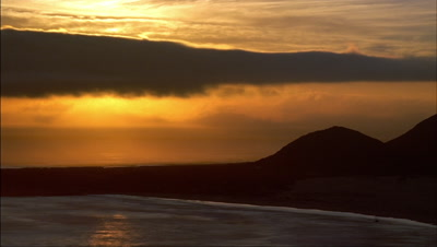 Wide angle sandy bay looking to opposite headland going into silhouette as sun sets orange