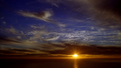 Medium wide angle clouds stream slowly towards camera over sea as sun sets orange