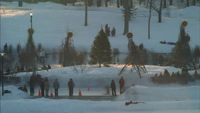 Medium wide angle people skating on frozen lake in park around a central island with simple modern Xmas trees