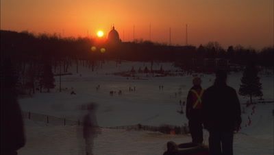 Medium wide angle spectators watching people below skating on frozen lake in park at dusk as orange sun setting behind church dome