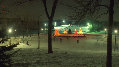 Medium wide angle looking down to people skating on frozen lake in park with illuminated simple modern Xmas trees -matches RK10221 and 10223