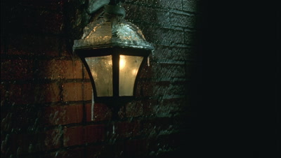 Mid shot ice forms on lit up outside lantern -black old fashioned- with red brick -matches RK 00064