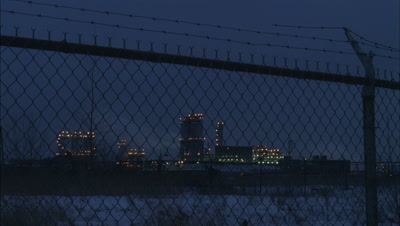 Medium wide angle Esso oil refinery viewed through tall wire mesh fencing as dusk turns to night