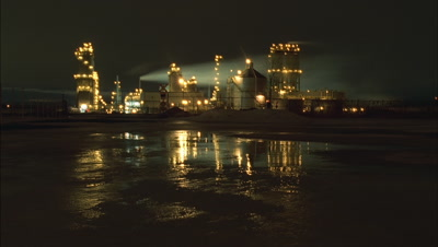 Wide angle Esso oil refinery all lit up at night with reflection in puddles and streaming chimneys