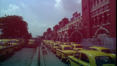 Medium wide angle street filled with streams of yellow taxis -rear view- pulling up to busy taxi rank outside Howrah Railway Station -Kolkata