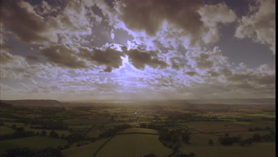 Wide angle rain clouds and sun rays move rapidly towards camera over British countryside, fields and hills with glimpses of River Severn from Coaley Peak viewpoint