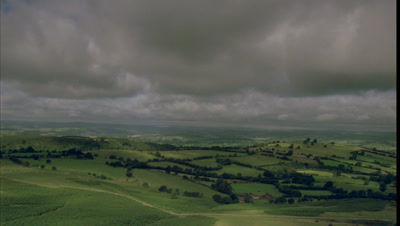 Medium wide angle panning shot from high point over rolling green fields and hedgerows with low grey cloud, sunshine and cloud shadows racing from Hay Bluff
