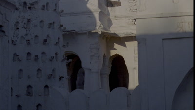 Close up white traditional Indian temple detail with window as sun and shadows move across wall