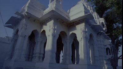 Mid shot white traditional Indian temple detail with multi columned porch and hanging balconies as sun and shadows move over