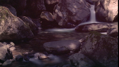Close up tree shadows move over motion blur water flowing over rocks in mountain stream -matches RK 10279