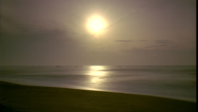 Medium wide angle sun rises out of darkness over smooth silvery sea with small boats bobbing on water and empty beach