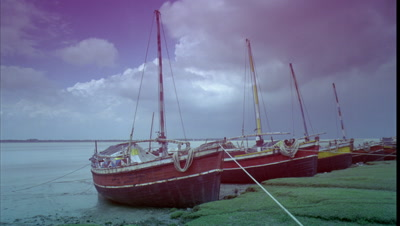 Medium wide angle fishing boats tied up by bank of Ganges with clouds racing overhead becoming stormy