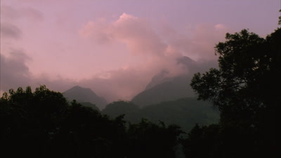 Medium wide angle looking up to peaks of Ruwenzoris as pink sun fades and cloud dissipates