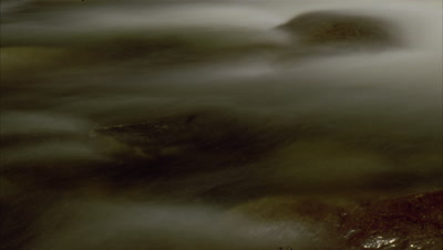 Big close up motion blurred water - abstract detail of fast flowing mountain stream