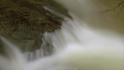 Big close up pan right over motion blurred water flowing over rock
