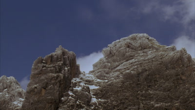 Mid shot looking up at Mt Stanley's granite peaks with dusting of snow with blue sky and fluffy white clouds