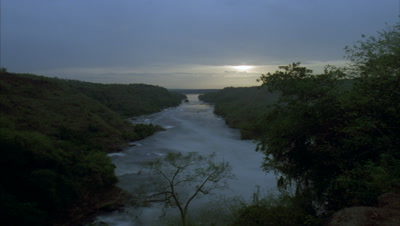 Medium wide angle looking down the river Nile towards Lake Albert from Murchison Falls as sun sets to darkness