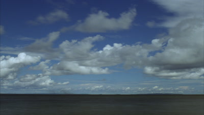 Wide angle blue sky with small fluffy white clouds streaming over grey water building to expansive cloud cover then clearing