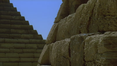 Close up stone step detail of Meroe Pyramids as sun and shadows move over stone with blue sky