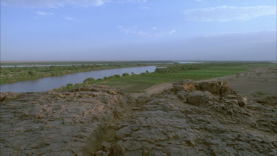 Wide angle black night sky lifts to morning light revealling view from rocky outcrop along River Nile showing desert meeting green cultivation belt