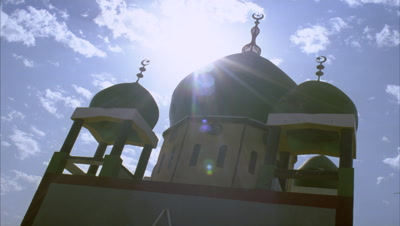 Low wide angle 3 domes of colourfully painted mosque topped with crescent moon and stars against sky with sun and clouds moving over