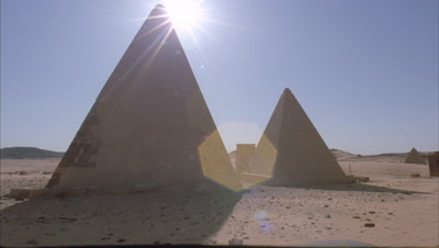 Medium wide angle from black night sky, sun rises over 2 pyramids emerging from behind them into clear blue sky