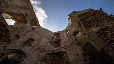 Abstract view of British Castle ruins on a sunny day with clouds passing over head. This is the inside of a castle featured in another clip.
