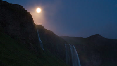 Icelandic Gullfoss waterfalls lit by moon light with heavy fog coming in and then clearing. Shot runs for duration and you see the fog clear to revel the landscape again. This is a different angle than most shots of the falls.
