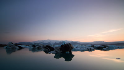 Sunset time-lapse at Jokulsarlon,an Icelandic glacial lagoon. Interesting foreground comprising of large icebergs with mountains in distance. Good colour change in the sky and gradual darkening.